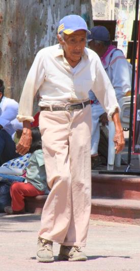 A viejo walks a cobblestone street in Chapala