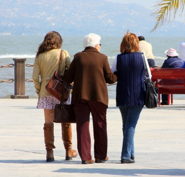 Three generations walk arm in arm along Jocotopec's malecon