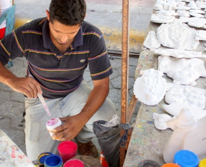An artisan prepares to apply color to plaster masks