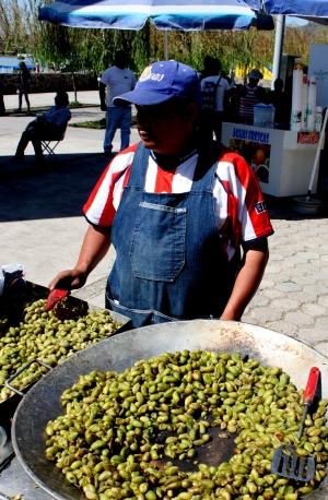 A street vendor cooks unshelled garbanzo beans
