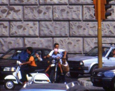 Ubiquitous Vespas weave through street traffic