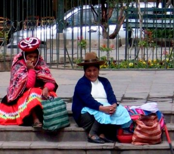 Two women in native dress wait for tourists to arrive