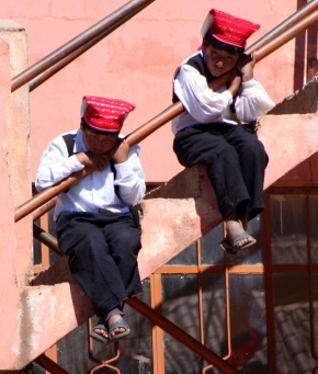 Two boys watch from a staircase vantage point