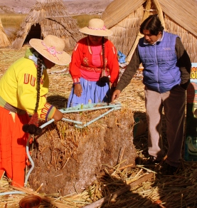 Uro women show how root blocks of floating reeds are lashed together.