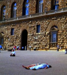 Tourists sun themselves in front of the Pitti Palace, Florence, Italy