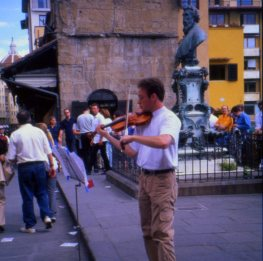 Musician plays for tips on the Ponte Vecchio, Florence, Italy.