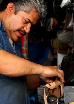 A cobbler works leather into footwear.
