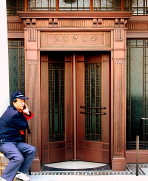 A century of history separates the cellphone talker and revolving door.